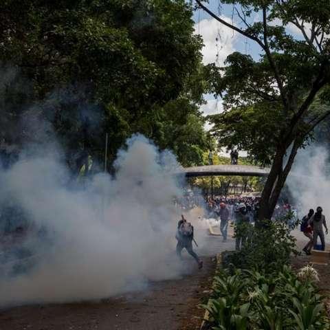 Decenas de manifestantes que estaban encapuchados y que se encontraban en una de las entradas de la UCV también se enfrentaron devolviendo los gases lacrimógenos a los efectivos de la Guardia Nacional Bolivariana.  /  Foto: EFE