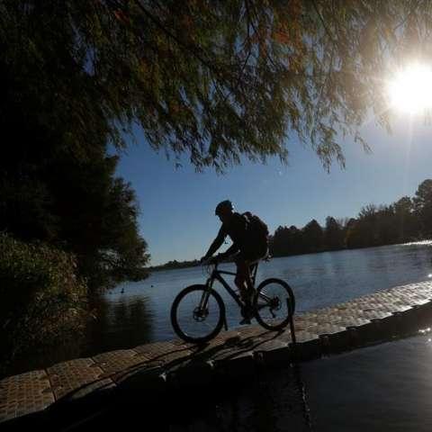 Los ciclistas montan sobre un puente flotante que cruza la presa de Emmarentia durante la Juma anual (aventura urbana de la bici de montaña de Johannesburg), Johannesburg, Suráfrica.  /  Foto: EFE