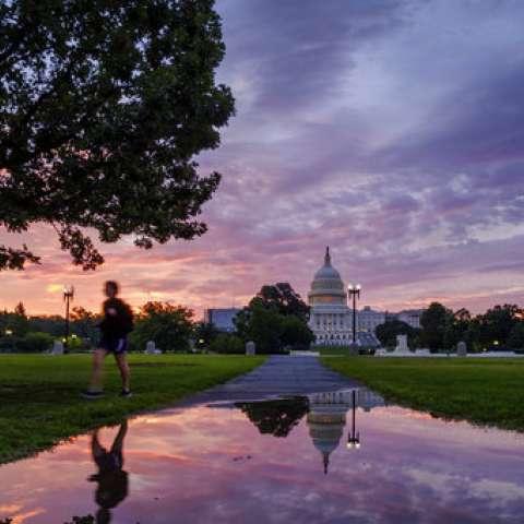 Un peatón pasea por un reflejo del Capitolio de Estados Unidos en un charco de lluvia al amanecer en Washington.  /  Foto: AP