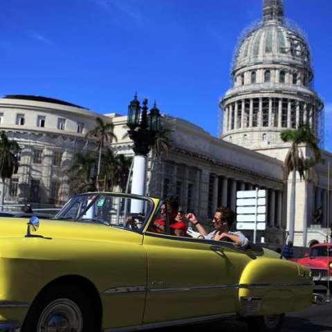 Dos turistas pasean en un viejo auto descapotable por una calle de La Habana (Cuba). EFE