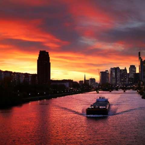 Un pequeño carguero llega a lo largo del río Main cuando se pone el sol en Frankfurt, Alemania. / AP