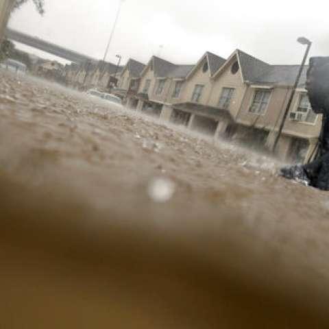 Un niño se abre camino a través de las aguas de la tormenta tropical Harvey mientras mira a los vecinos en su complejo de apartamentos en Houston.  /  Foto: AP