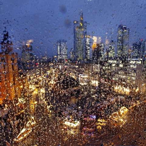 La iglesia Katharinen fue, el mercado de Navidad y los edificios de los bancos se ven detrás de una ventana cubierta con gotas de lluvia en una tarde lluviosa en Frankfurt, Alemania. / Foto: AP