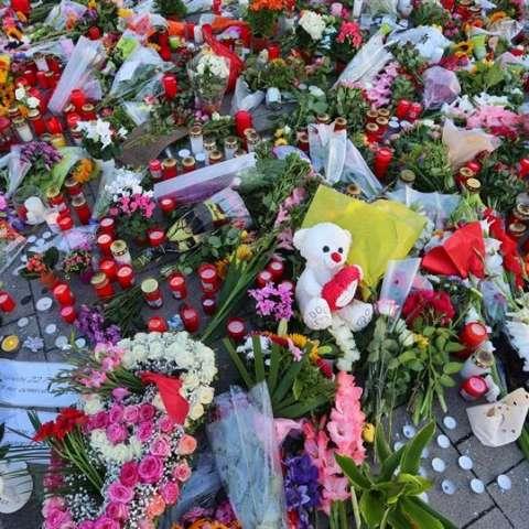 Flores, velas y peluches despositadas en la entrada del centro comercial de Múnich en el que el pasado viernes un joven mató a nueve personas y posteriormente se suicidó.  / Foto: EFE