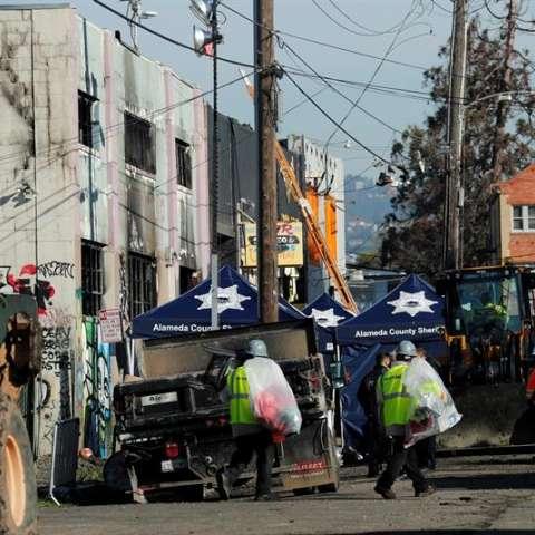 La Policía y los bomberos trabajan, este 4 de diciembre de 2016, en el lugar de acceso a un almacén donde se celebraba un concierto en el barrio de Fruitvale en Oakland (California), donde murieron 33 personas en un incendio el pasado 2 de diciembre. EFE