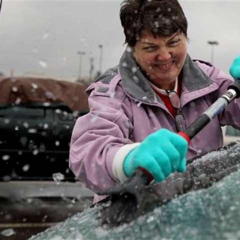 Mary Zinser retira el hielo acumulado en el parabrisas de su vehículo el viernes 13 de enero de 2017 en Arnold, Missouri.  /  Foto: AP