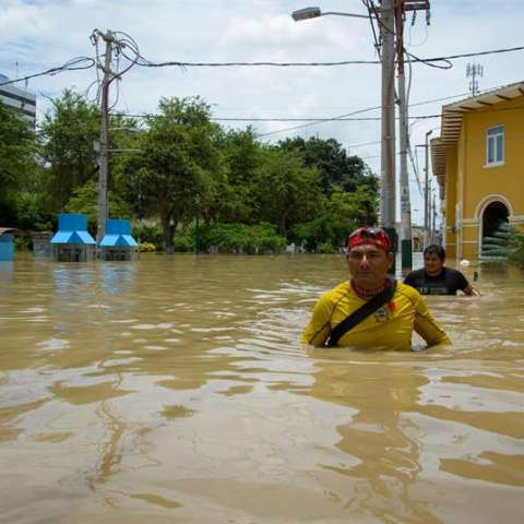 Dos hombres intentan cruzar una calle inundada por el río Piura este 27 de marzo de 2017, en Piura (Perú). EFE