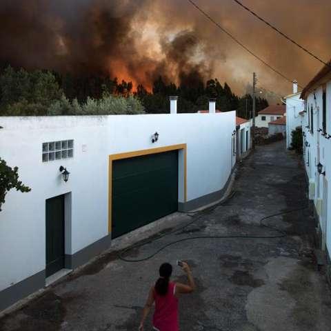 Una mujer es vista cerca de un incendio forestal en Quinta das Laranjeiras, en Vila do Rei, Castelo Branco, (Portugal). EFE. / Foto: EFE