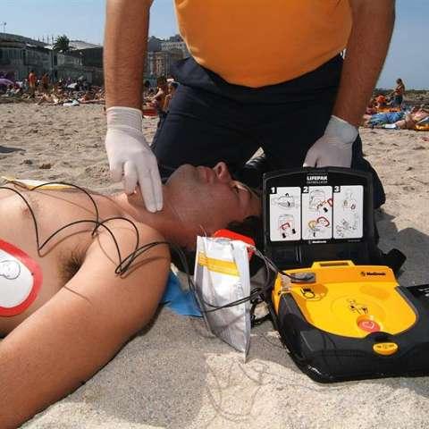 Un miembro de Protección Civil practica un simulacro del uso de un desfibrilador semiautomático externo (DESA) para los paros cardiacos en la playa de Riazor en A Coruña (España). EFE/Archivo