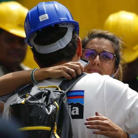 Un trabajador de rescate abraza a la novia de Jorge Gómez, de España, que espera en el sitio de búsqueda de personas que se cree están atrapadas bajo los escombros de un edificio de oficinas colapsado, incluido su novio.  /  Foto: AP