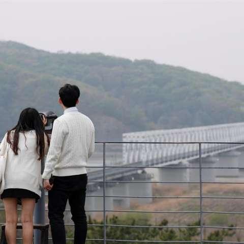Dos turistas observan el lado norcoreano a través de unos binoculares en la zona desmilitarizada (DMZ) en Paju (Corea del Sur). EFE