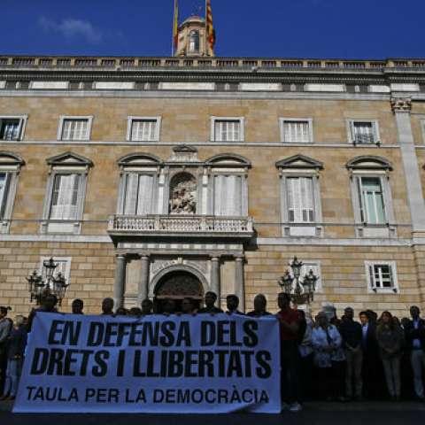 """La gente sostiene una pancarta que lee en catalán: """"En defensa de los derechos y libertades"""". Mesa para la democracia """"./ AP"""