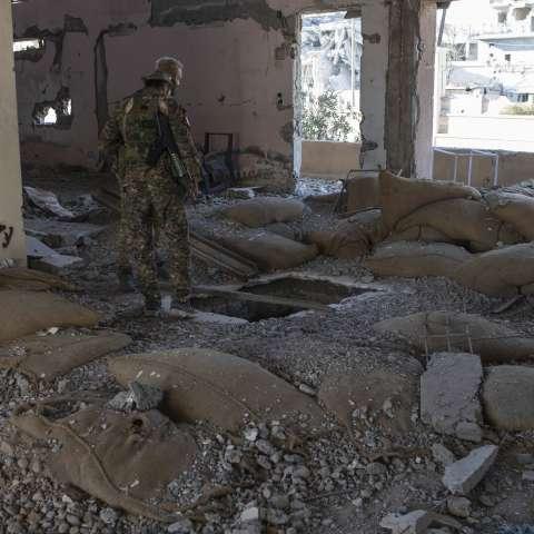 Miembros de las Fuerzas Democráticas Sirias respaldadas por los Estados Unidos comprueban si hay bombas en el estadio que fue el último puesto de los combatientes del Estado Islámico en la ciudad de Raqqa, Siria. / AP