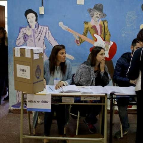 Un votante presenta sus documentos a los trabajadores electorales antes de ingresar a una cabina de votación durante las elecciones legislativas de mitad de período en Buenos Aires, Argentina. / AP