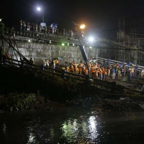 Miembros de fuerzas de rescate y efectivos del ejército indio examinan el lugar en el que un puente se ha derrumbado en Calcuta (India) hoy. AP