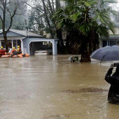 Un hombre está con en el agua a la altura de la cintura mientras toma las imágenes de los teléfonos celulares de las cuadrillas de rescate. / Foto: AP