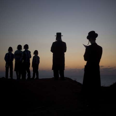 Los judíos ultraortodoxos de la secta Hassidic de Vizhnitz oran sobre una colina que domina el mar Mediterráneo mientras participan en una ceremonia Tashlich en Herzeliya, Israel. / AP