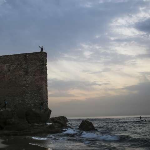 Un hombre toma un selfie en las murallas de las antiguas murallas medievales de Assilah, una ciudad costera en Marruecos. / AP
