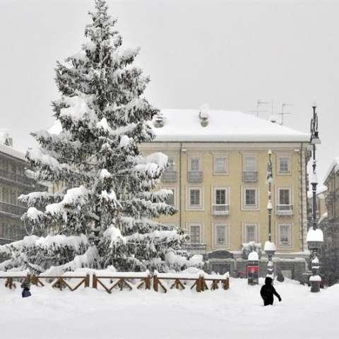 Varias personas cruzan una plaza cubierta por una gruesa capa de nieve en Aosta, Italia.  EFE
