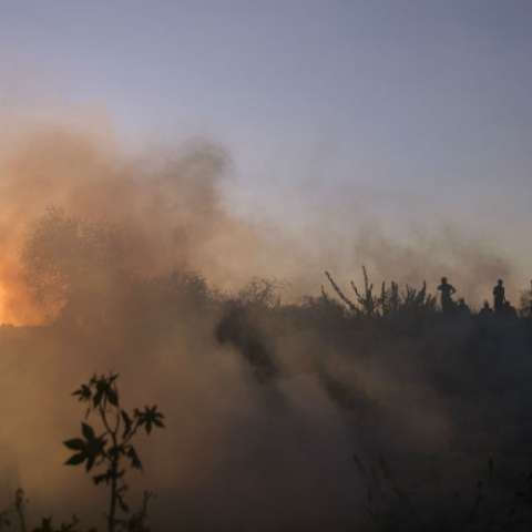 Manifestantes palestinos huyen de los gases lacrimógenos disparados por las tropas israelíes durante una protesta en la entrada del cruce fronterizo de Erez entre Gaza e Israel, en el norte de la Franja de Gaza. AP