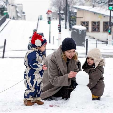 Una madre y sus dos niños juegan en la nieve cerca del cementerio Pere Lachaise, cerrado por la nieve en París (Francia). EFE
