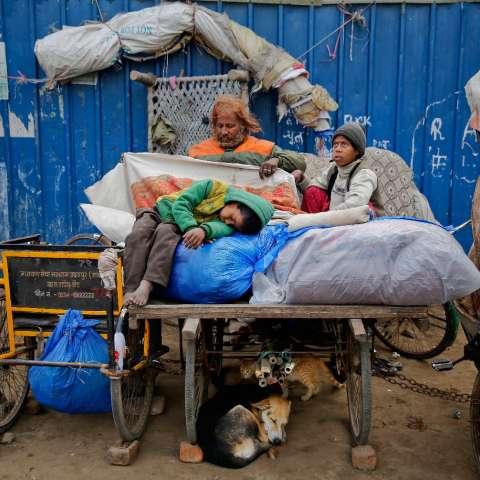 Farmaan, de 7 años, se queda dormido en un montón de sus pertenencias colocadas en un carrito de madera del vendedor de frutas, que ellos llaman su hogar, en Nueva Delhi, India, el 1 de febrero de 2019. (Foto AP / Altaf Qadri)