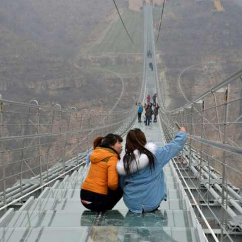 BASCHAN (CHINA), 05/01/2018.- Dos mujeres se sacan una fotografía en el nuevo puente de cristal más largo del mundo, que atrae a diario a miles de intrépidos en el noreste de China. EFE/ Alvaro Padilla