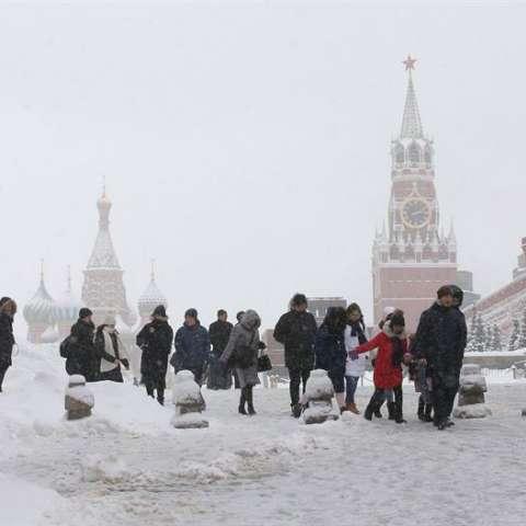 Varios turistas caminan por la Plaza Roja, cubierta por la nieve, tras una jornada de fuertes nevadas en Moscú (Rusia). EFE