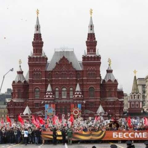 """La gente lleva retratos de parientes que lucharon en la Segunda Guerra Mundial, banderas rusas y soviéticas y una pancarta que dice """"Regimiento Inmortal"""", durante la marcha del Regimiento Inmortal a lo largo de la Plaza Roja en Moscú, Rusia.  AP"""