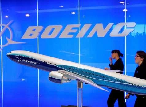 El personal de Boeing pasa junto a un modelo de avión de Boeing en exhibición en el Singapore Airshow en Singapur. EFE