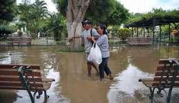 Vista de una pareja caminando en la inundada Plaza de Armas de la ciudad de Piura a unos 1000 kms. al norte de Lima (Perú). EFE