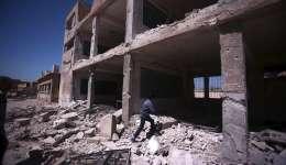 Un niño inspecciona un colegio en ruinas tras unos bombardeos en el pueblo de Deir al Asafi, al sureste de Damasco (Siria).  /  Foto: EFE Archivo