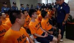 El director general de la Policía Nacional filipina, Ronald Dela Rosa (dcha), conversa con los extranjeros arrestados por su presunta implicación en un secuestro en el cuartel general de la policía en Quezon, este de Manila (Filipinas). EFE/Archivo