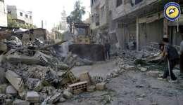 Ciudadanos limpian los escombros en una calle un día después de los ataques aéreos, en el suburbio de Damasco Arbeen.  /  Foto: AP