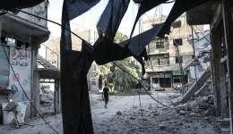Un hombre camina junto a los escombros de casas destruídas por los bombardeos de aviones de guerra no identificados en Arbin, a las afueras de Damasco (Siria), el pasado mes de julio. EFE/Archivo