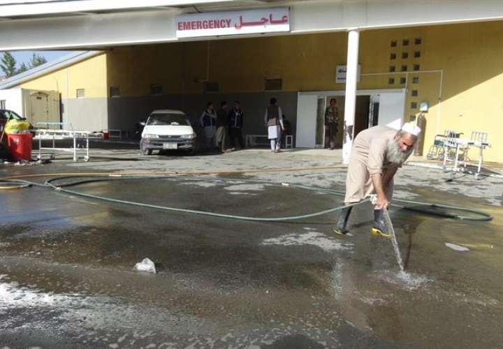 Operarios limpian el área de entrada al hospital donde fueron desplazadas las víctimas de un ataque suicida, en la provincia de Paktia (Afganistán). EFE