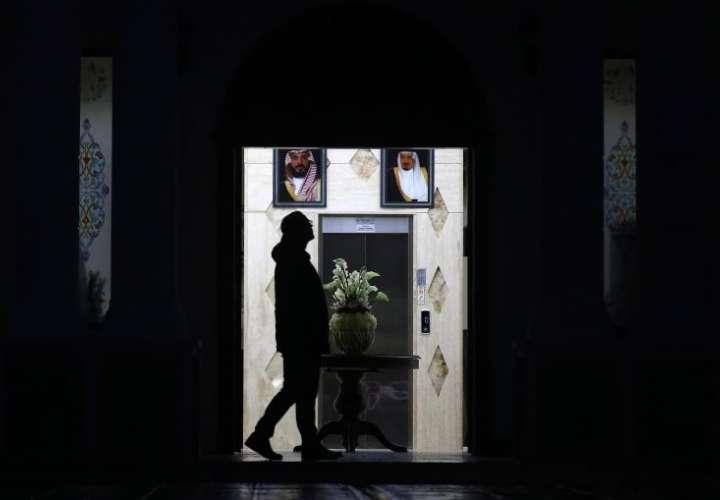 Un agente forense turco caminaba frente a la fotografía del príncipe heredero Mohammed Bin Salman (i), y del rey de Arabia Saudí Salman bin Abdulaziz Al Saud (d), durante un registro en una finca en Yalova (Turquía), la semana pasada. EFE