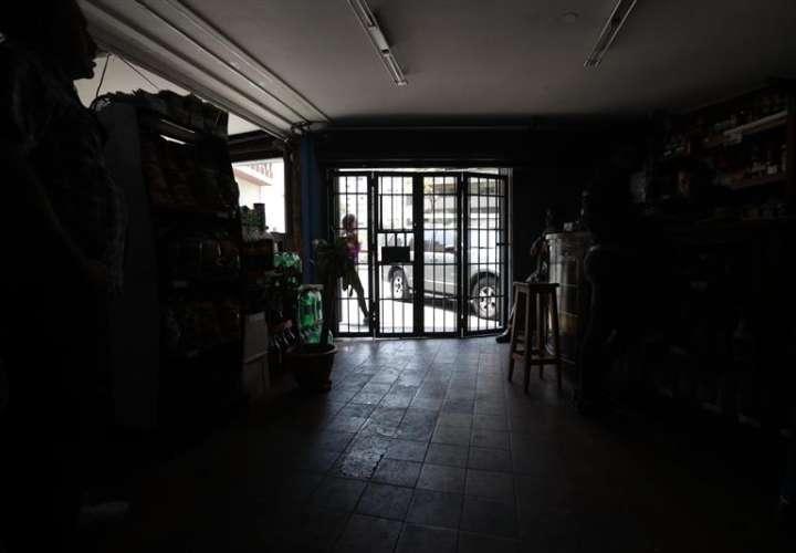 Fotografía del ingreso a un edificio sin energía eléctrica en horas de la noche. EFE