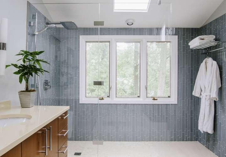 La diseñadora de interiores Nadia Subaran dice que los propietarios de viviendas cada vez más quieren duchas con mampara de vidrio en las que puedan caminar directamente sin ningún paso ni puerta, como se ve en este diseño de Aidan Design. AP