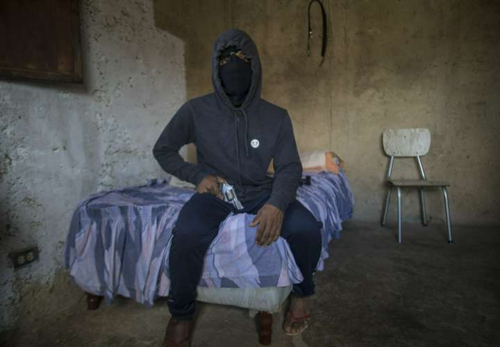 """Un gángster enmascarado que recibe el apodo de """"El Negrito"""" posa para un retrato con su arma dentro de la casa de seguridad de su pandilla en el barrio de Petare en Caracas, Venezuela, el lunes 13 de mayo de 2019.  AP"""