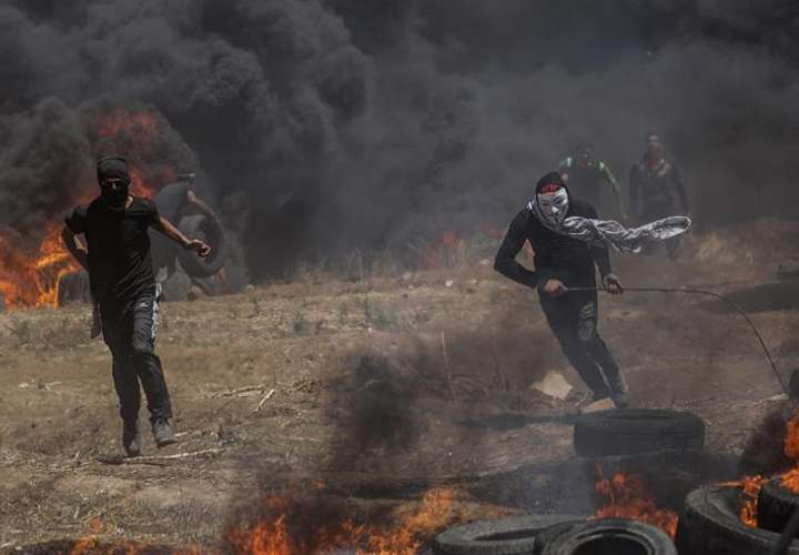 Dos palestinos corren en busca de refugio durante los enfrentamientos surgidos tras las protestas convocadas cerca de la frontera con Israel en el este de la franja de Gaza, hoy, 14 de mayo de 2018. EFE