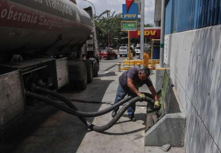 Un trabajador prepara las mangueras de un camión cisterna para llenar tanques de combustible, este viernes, en una estación de servicio de Caracas (Venezuela). EFE