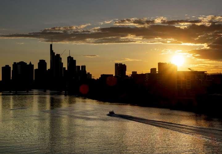 Una lancha rápida corre sobre el río Main con el distrito bancario en el fondo mientras el sol se pone en Frankfurt, Alemania. (Foto de AP)