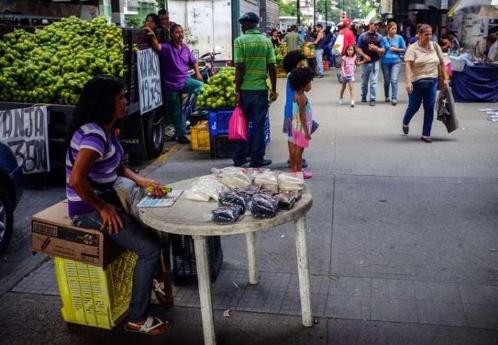 vendedora informal mientras espera por clientes en un puesto en una calle de Caracas (Venezuela). EFE