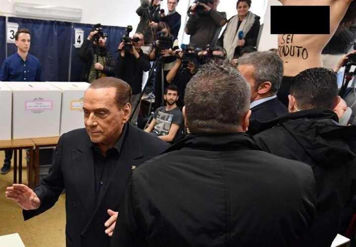 Exprimer ministro italiano y líder del partido 'Forza Italia', Silvio Berlusconi (izq.), Deja la mesa de votación cuando un activista 'Femen' (R) presenta una protesta con el torso desnudo durante la votación en las elecciones generales. EFE