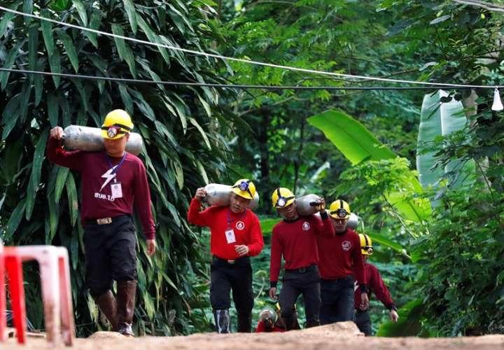 Miembros de los servicios de rescate cargan con botellas de oxígeno mientras continúan las labores de rescate de los doce menores y un adulto atrapados en una cueva en el parque de Khun Nam Nang (Tailandia) . EFE