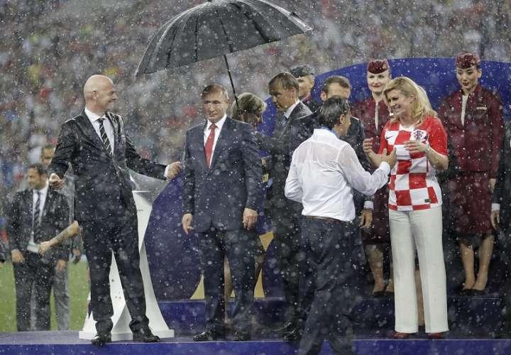 Gianni Infantino (izq.) comenzó a reírse a carcajadas al observar que el único que tenía paragua era Vladimir Putin. Foto AP