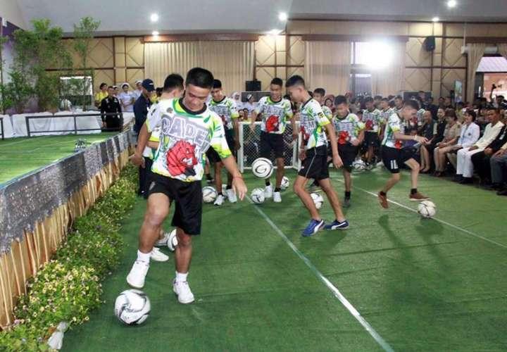 Los doce niños y su entrenador rescatados del interior de una cueva en el norte de Tailandia muestran sus habilidades futbolísticas durante su primera aparición pública junto a psicólogos infantiles, después de que abandonaran el hospital. EFE