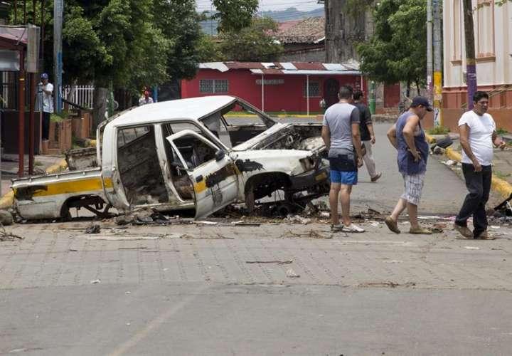 Ciudadanos pasan frente a un coche quemado, en la ciudad de Masaya (Nicaragua). EFE Archivo