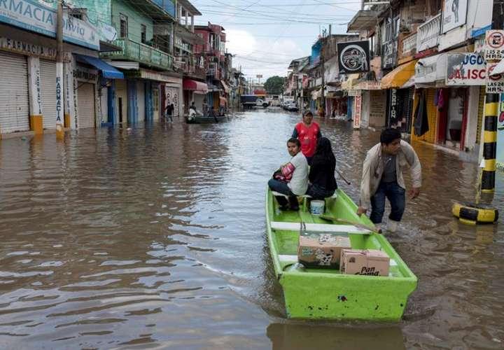 Habitantes de la ciudad de Minatitlán, en el estado de Veracruz(México), utilizan barcazas para cruzar las calles inundadas por las tormentas que afectan a buena parte de territorio mexicano, además de la llegada del huracán Willa. EFE